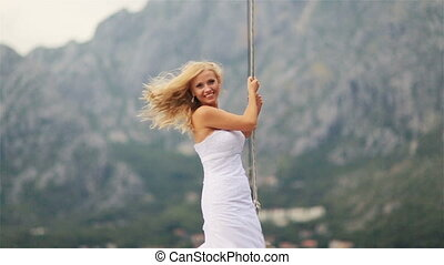 Charming blond bride posing  at the stern of vintage yacht sailing on the sea in Montenegro, Budva