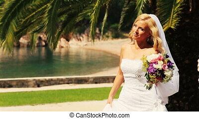 Charming blond bride walking with flowers on Montenegro, Budva