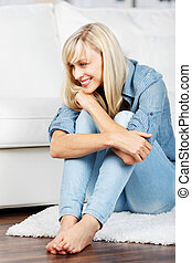 Charming blond woman sitting on the floor and looking at ...