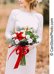 Charming blonde bride posing in the autumn forest with bouquet of roses