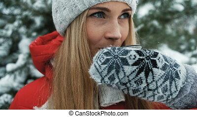 Charming blonde has hot tea against background of winter landscape