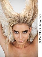 Charming blonde model in black dress posing holding her hair...