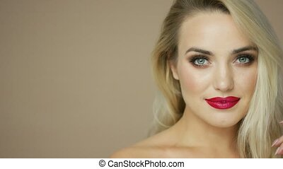 Charming blonde model with red lips - Studio portrait of...