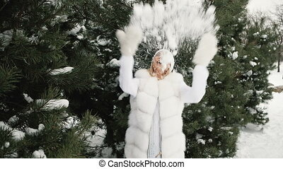 Charming blonde plays with snow against background of winter landscape