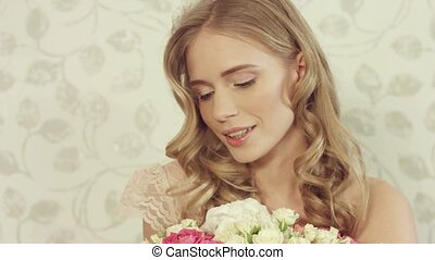 Charming blonde with wavy hair posing with a large bouquet...