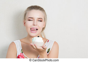 Charming blonde woman enjoying sweet dessert with butter cream. Space for text