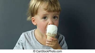 Charming boy eating ice-cream cone