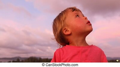 Charming boy in sunset looking around - Side view of little...