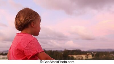 Charming boy in sunset looking away - Side view of little...