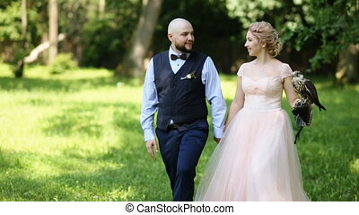 Charming bride and groom on the background of forest with an eagle sitting on her arm