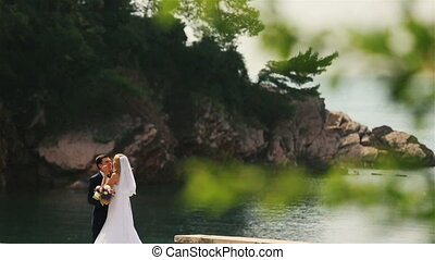 Charming bride and groom softly kissing with the wonderful seascape of Montenegro, Budva on background