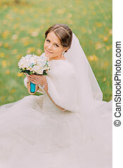 Charming bride in gorgeous white dress with long veil sitting on grass holding wedding bouquet