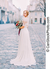 Charming bride in long lace dress holding vintage bouquet looking over shoulder into the camera with old city architecture on background
