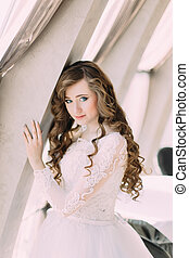 Charming bride in white dress and with curly hairstyle posing near window at cafe, close-up