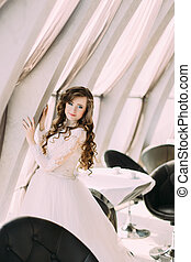 Charming bride in white dress and with curly hairstyle posing near window at cafe