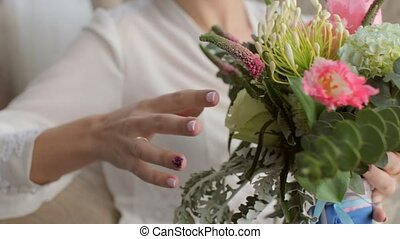 Charming bride sitting in the chair with the wedding bouquet in the hands