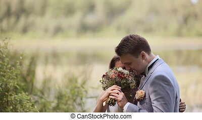 Charming bride with a bouquet and her fiance together on nature. Tenderness of relations. Kiss. Happy together. Wedding day.