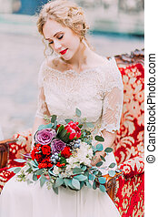 Charming bride with blonde curly hair sits on red vintage armchair and looks on her beautiful wedding bouquet with roses and peonies