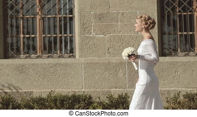 Charming bride with bouquet goes toward the bridegroom -...