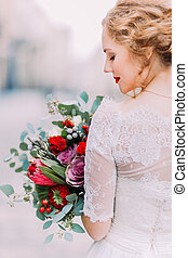 Charming bride with long hair looks on her wedding bouquet (back view)