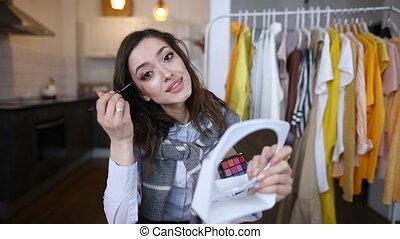 charming brunette blogger leads a video tutorial online. ...