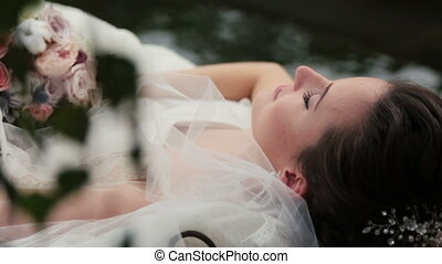 Charming brunette bride lying in the boat with eyes closed close up. Wedding bouquet in hands