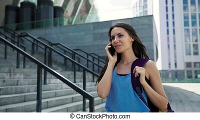 Charming brunette girl in sportswear and with sports bag talking on mobile phone, walking after training