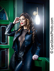 Charming brunette in black leather outfit with green painted...