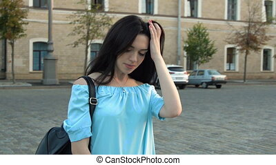 charming brunette in blue blouse stands on the street and...