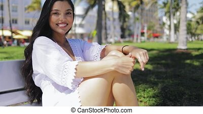 Charming brunette in dress sitting on bench - Young charming...