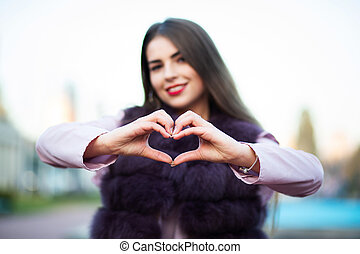 Charming brunette model showing heart symbol with two hands over a city background