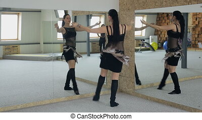 Charming brunette practices belly dance in front of mirror....