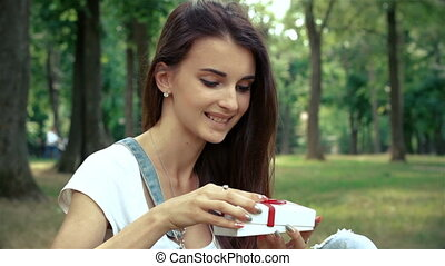 charming brunette sits on the grass and watches gift