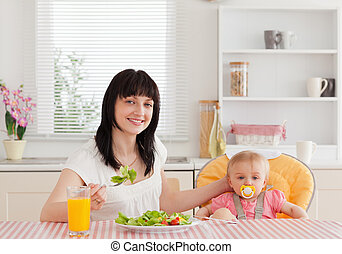 Charming brunette woman eating a salad next to her baby while sitting in the kitchen