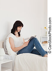 Charming brunette woman reading a book while sitting on a bed