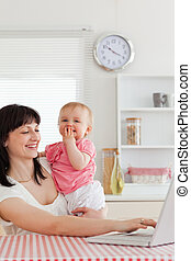 Charming brunette woman relaxing with her laptop next to her baby while sitting in the kitchen