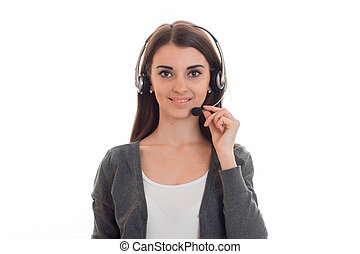 Charming brunette woman working in call center with headphones and microphone smiling on camera isolated on white background