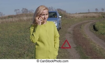 charming business woman calls for help by mobile phone. girl near broken car on rural road. 4K