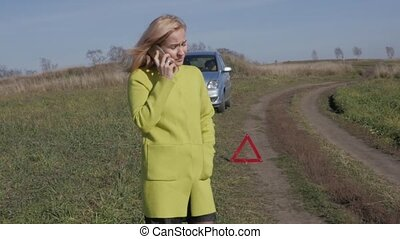 charming business woman calls for help by mobile phone. girl near broken car on rural road. slow motion