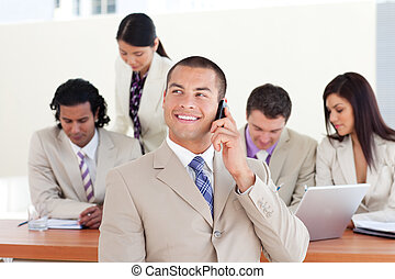 Charming businessman in a meeting with his team in the background