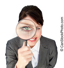 Charming businesswoman looking through magnifying glass