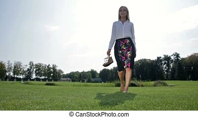 Charming businesswoman relaxing on the green grass
