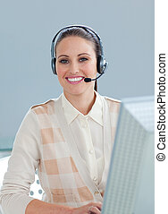Charming businesswoman with headset on working at a computer...