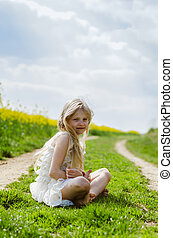 charming caucasian child sitting alone in spring nature