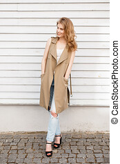 Charming cheerful young woman in a light summer vest in a stylish T-shirt in blue ripped jeans in black shoes with high heels and a leather bag posing at the wooden white vintage wall. Happy girl