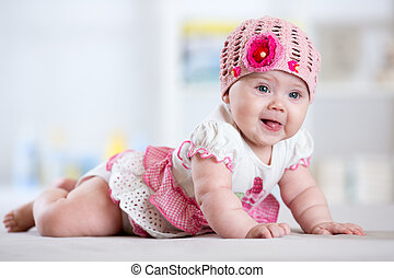 Charming child little girl with hat lying on her stomach