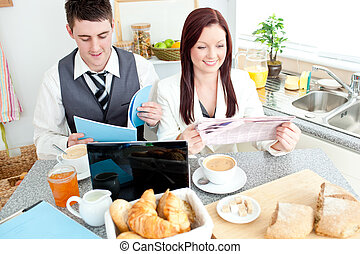 Charming couple of businesspeople having breakfast in the kitchen at home