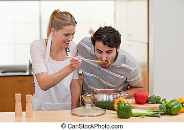 Charming couple preparing a sauce in their kitchen