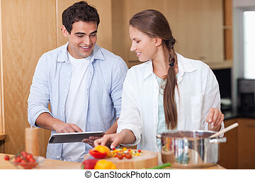 Charming couple using a tablet computer to cook