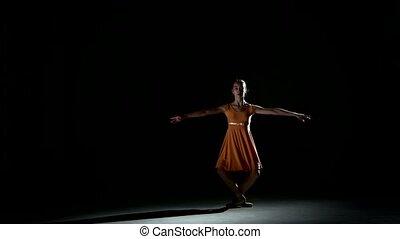 Charming curly girl dancing ballet in studio